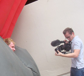 Mark Walley films Jimmy Kuehnle as he struggles down the street in an inflatable suit.