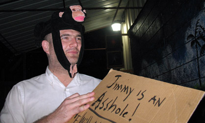 Closup of George Zupp holding a sign wearing a monkey hat.